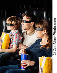 Family Having Snacks While Watching 3D Movie
