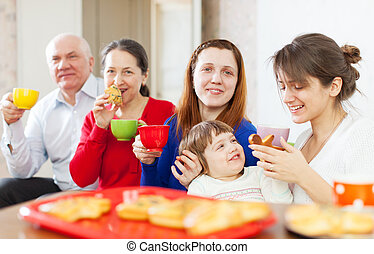family having tea with cakes   together