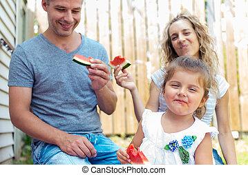 Family having watermelon on a picnic