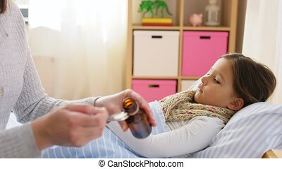 family, health and people concept - mother pouring cough syrup for sick daughter lying in bed at home