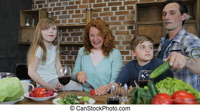 Family Helping Mother With Cooking Together In Kitchen Parents With Two Kids Preparing Food At Home Talking Chopping Vegetables For Salad