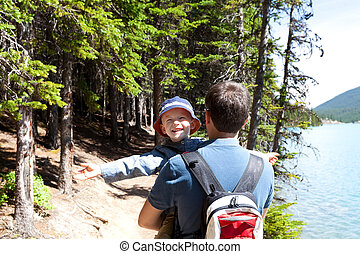 laughing excited boy and his father hiking at moraine lake, banff national park, canada