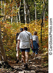Sunday family hiking in a trail in autumn