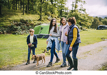 Family are leaving the campsite they are staying in to go for a hike with the dog.