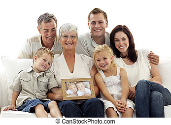 Family holding a portrait of children sitting on sofa at...