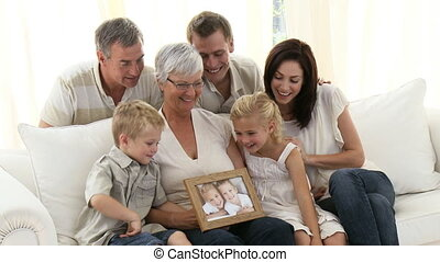 Family holding a portrait of children sitting on sofa