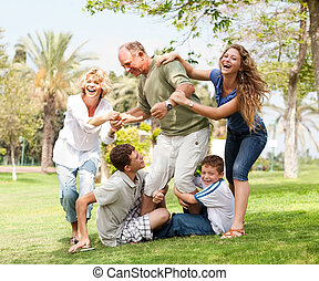 Family holding back grandfather and having fun -...
