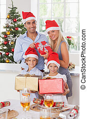 Family holding christmas presents - Family wearing santa...