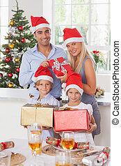 Family holding christmas presents - Family wearing santa...