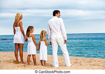 Family holding hands on beach.