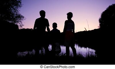 family holding hands together and looks at pond