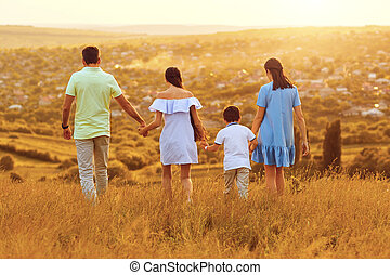 Family holding hands walking in nature at sunset.