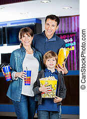 Family Holding Popcorns And Drinks At Cinema