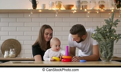family, holidays and people concept - happy mother, father and little daughter playing with ring pyramid baby toy on birthday party