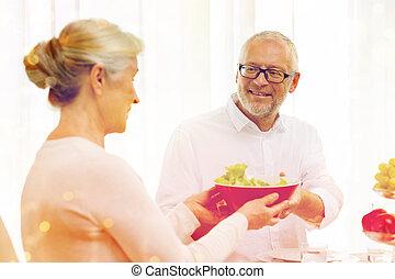 smiling senior couple having dinner at home