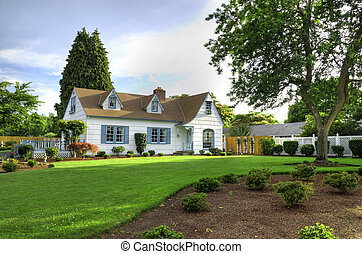 The front of a nicely kept family home with a green lawn and a tree to the right.