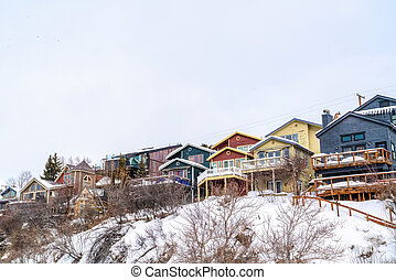 Family homes on a snowy mountain residential area against white sky in winter