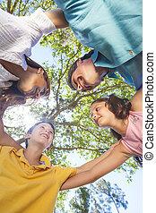 Family Huddle Together Outside In Sunshine