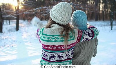 Family hugging in winter forest throwing snow and enjoying landscape. Mother and daughter having fun walking.