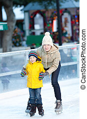 family ice skating - happy positive family of two ice...