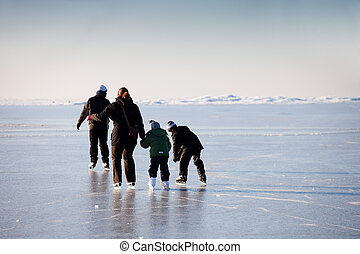 Family ice skating in natural rink frozen sea