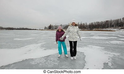 Family ice skating on frozen lake