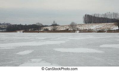 Family ice skating on frozen lake