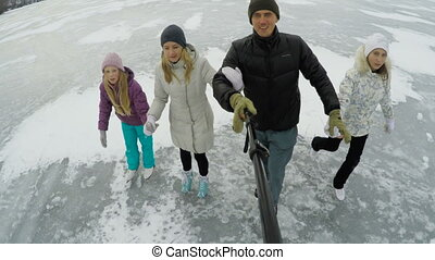 Family ice skating on frozen lake - happy family taking...
