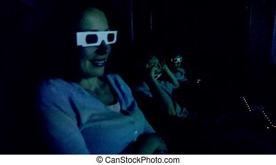 Family in 3d stereo glasses sit at cinema and watch movie