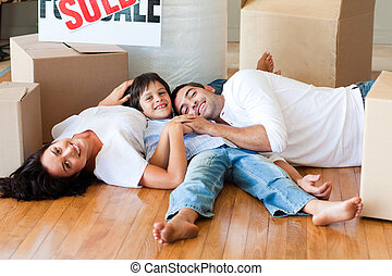 Family in a new house lying on floor with boxes