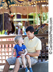 family in amusement park - young father and his little son...