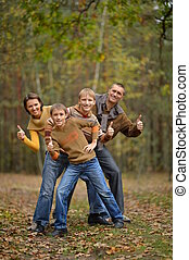Family in autumn forest with thumbs up