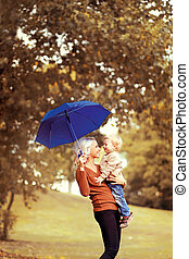 Family in autumn! Happy mother and child with umbrella having fun together