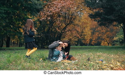 Family in autumn park. Funny cute little girl throws autumn yellow leaves on her mother and brother, little boy slow mo