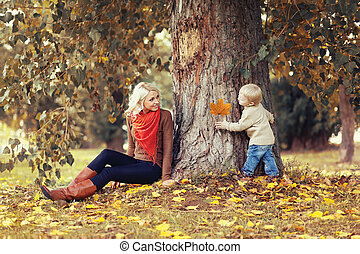 Family in autumn park! Happy mother and child having fun together