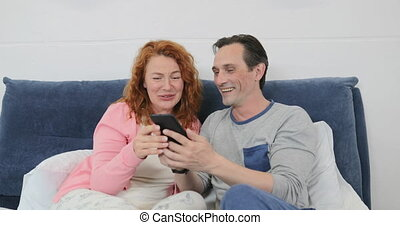 Family In Bedroom, Parents Using Cell Smart Phone While...