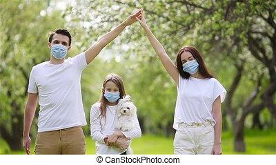 family in blooming cherry garden in masks