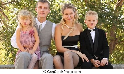 Family in celebratory clothes sits on bench.