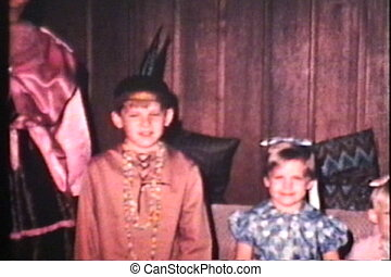 A cute family gets dressed up in crazy costumes to celebrate a special event and poses in their living room. (Scan from archival 8mm film)
