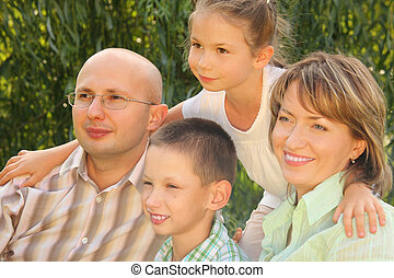 family in early fall park. dad, mom and little boy sitting at the grass. little girl is standing behind their. all of them is looking away