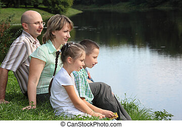 family in early fall park. father, mother, little boy and girl is sitting near pond.