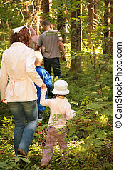 Family in forest looking for mushrooms