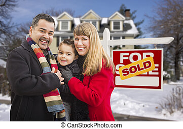 Family in Front of Sold Real Estate Sign and House - Warmly...