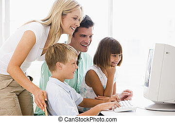 Family in home office using computer smiling