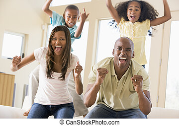Family in living room cheering and smiling
