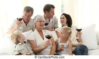 Family in living-room drinking wine and eating biscuits