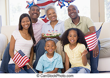 Family in living room on fourth of July with flags and...