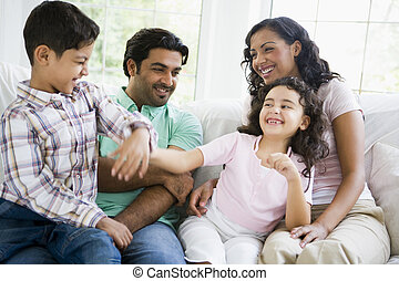 Family in living room play fighting and smiling (high key/selective focus)