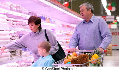 Family in mall near refrigerators - Grandparents and...