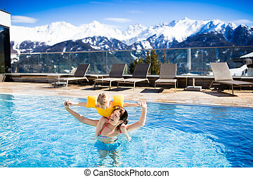 Family in outdoor swimming pool of alpine spa resort - ...